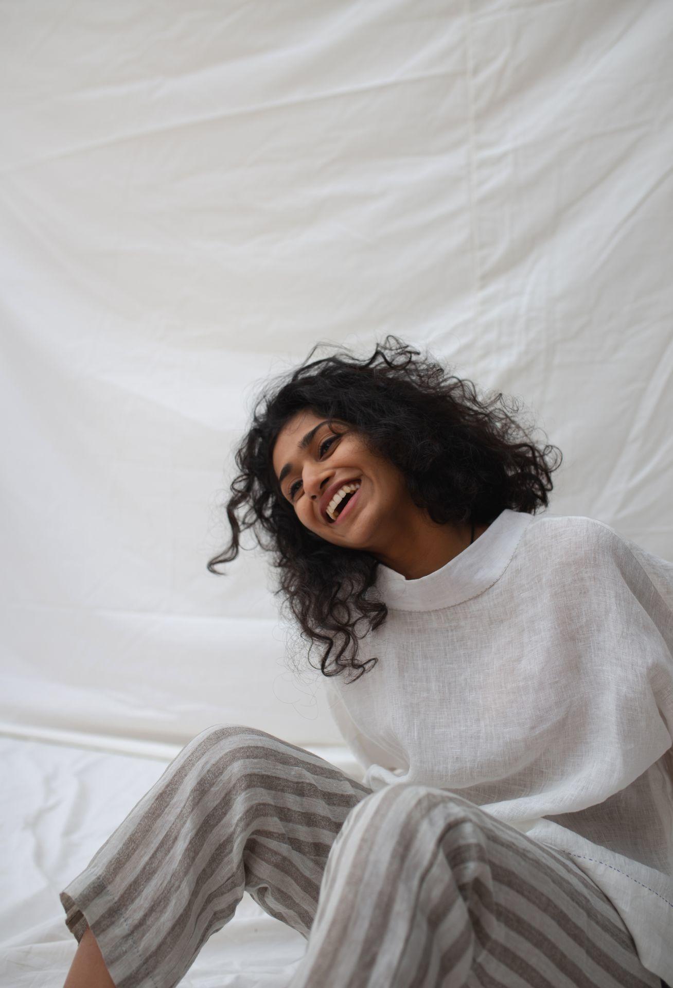 Sitting laughing posing smiling wearing white brand