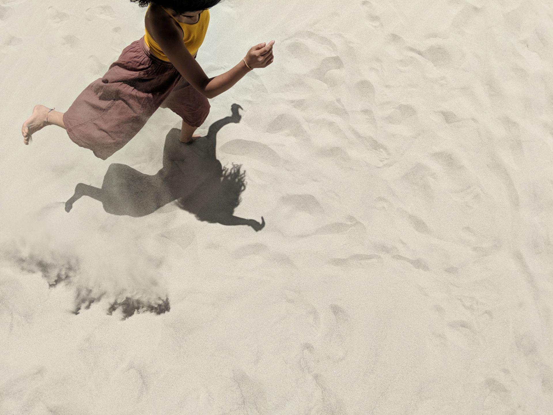 Swishing sand wearing yellow brown Ladakh dancing dance pose