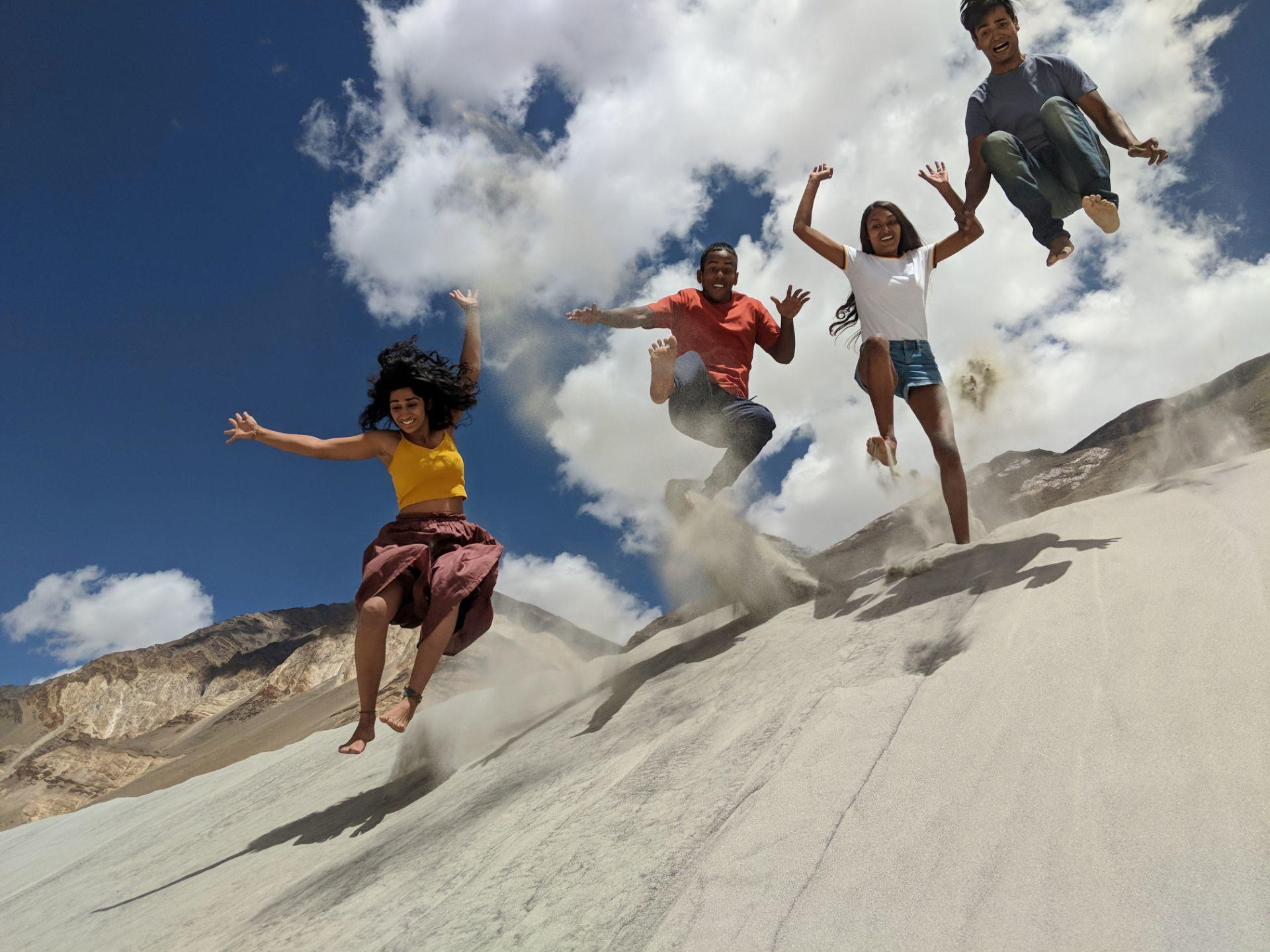 Four friend jumping on the sand and the shot is taken mid air in ladakh