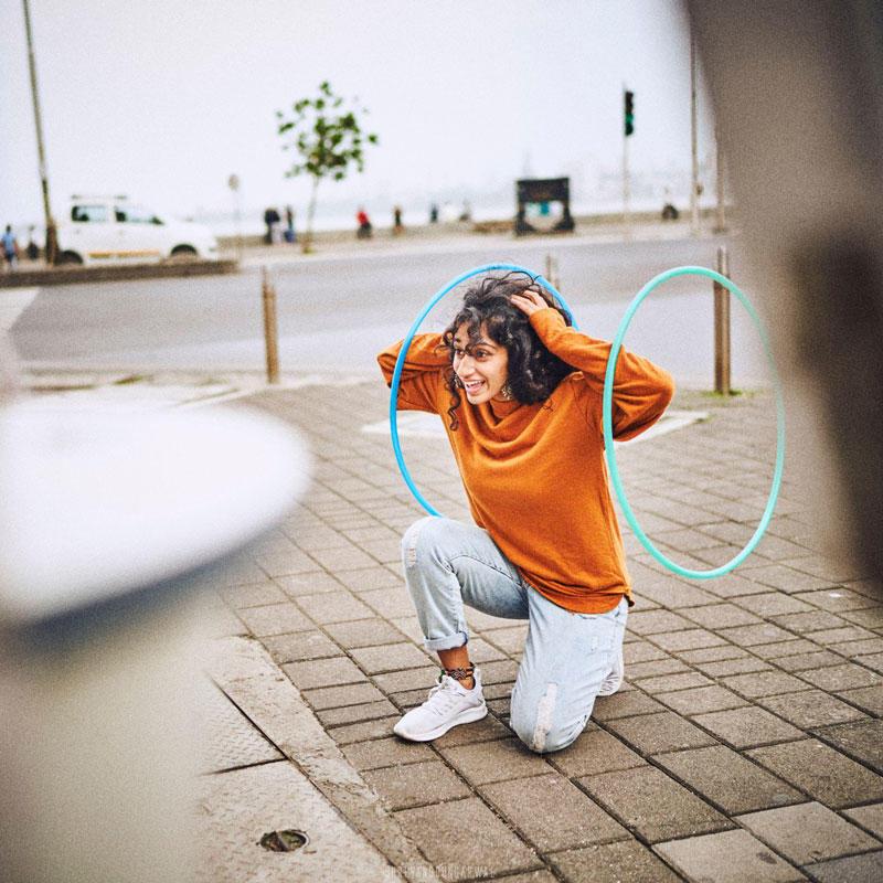 Double hoop flow dance posing restaurant outside beach mustard sweater